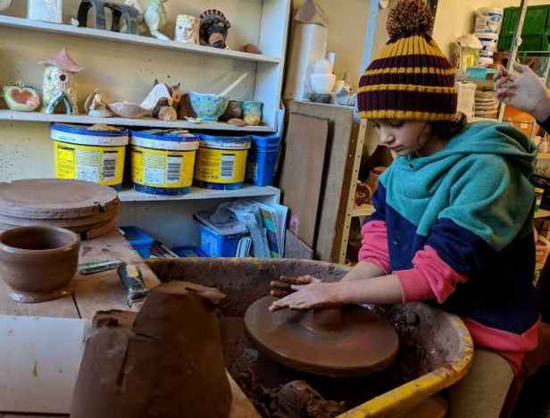 Image of girl in bobble hat using potters wheel