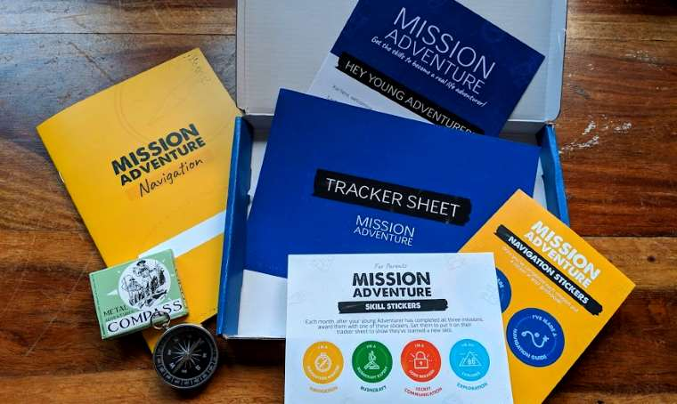 Image of open cardboard box with the words Mission Adventure written on vaarious blue, yellow and white paperwork, stickers and a silver metal compass