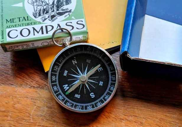 Image of silver metal compass on table with green box with words metal adventurer's compass written on