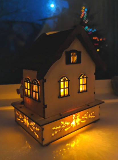 Image of LED lit wooden house on windowsill showing rear side lit up
