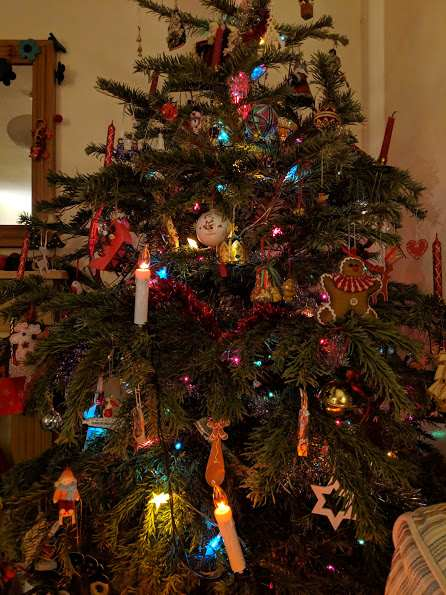 Image of decorated indoor evergreen Christmas tree including baubles, tinsel and white candle lights