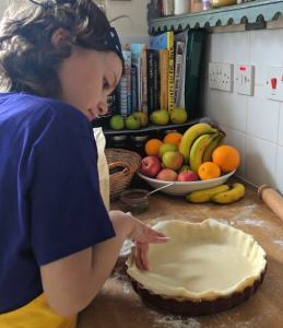 Image of girl in blue T-shirt shaping pastry into a flan dish on a floured surface with recipe books behind