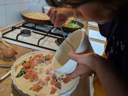 Image of girl pouring cream mixture into pastry and salmon filled flan dish