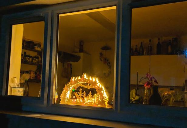Image of wooden windowsill Christmas silhouette light in house window viewed from outside