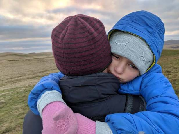 Image of child with sad face being carried on top of grassy hill with grey clouds behind