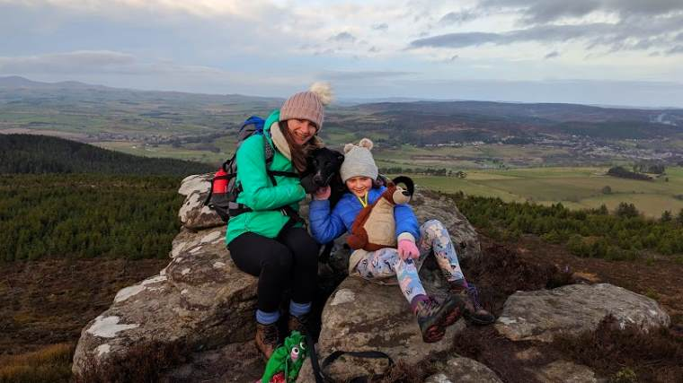 Image of woman and child in outdoor gear sitting with black dog on crags on Simonside hilltop with distant views