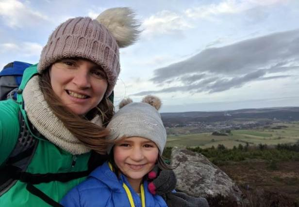 Image of woman and girl in outdoor coats and woolly hats on top of hill ridge with distant view behind