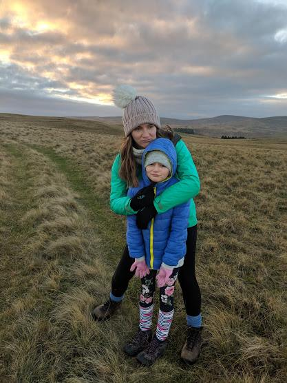 Image of woman in green top hugging child in blue coat on top of grassy hill with sunset sky behind