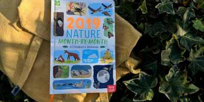 Image of 2019 Childrens' Month by Month Nature Almanac book in ivy hedge on yeloow canvas bag