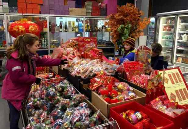 Image of 3 girls at sweet counter in shop with Chinese decorations