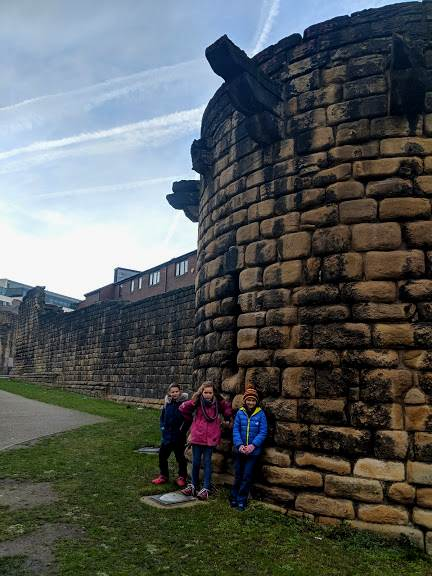 Image of 3 girls standing in front of old stone city walls in Newcastle, UK