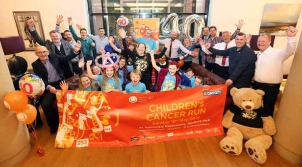 Image of group of adults, children and giant bear with arms raised in victory with silver 40th balloon and orange NECCR Children's Cancer Run banner