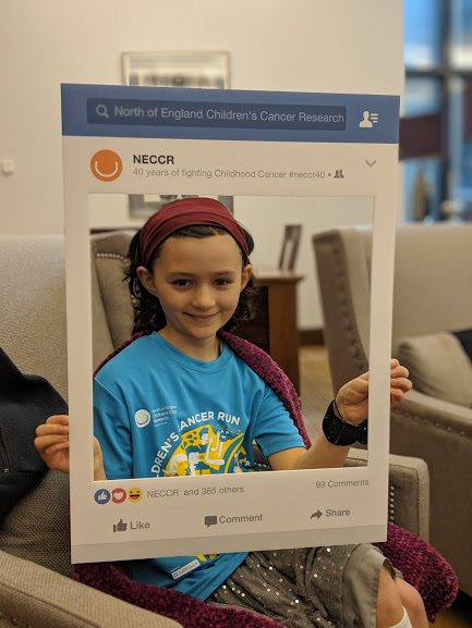 Image of smiling girl in blue T-shirt, silver skirt and red headband holding cardboard Facebook frame