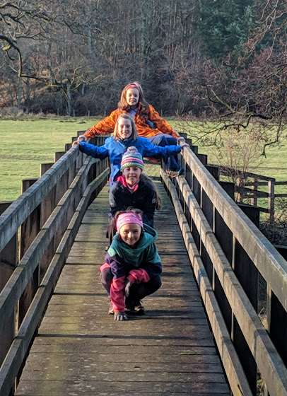 Image of 4 girls on a country walk wearing felted feet stood in a row at different heights on a wooden footbridge with field and woods in background