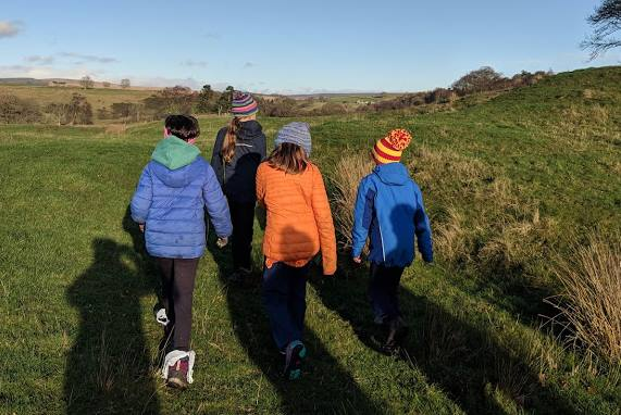 Image of four girls in bright outdoor clothing walking away from the camera with plastic bags sticking over the top of their walking boots