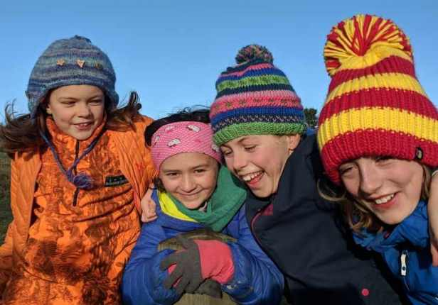 Image of four smiling girls faces in brightly coloured winter coats and bobble hats with blue sky behind