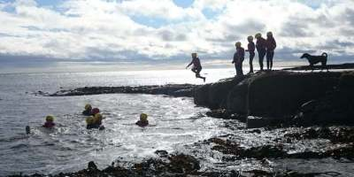 Group of children and adults in silhouette on rocks and in sea at shoreline jumping in
