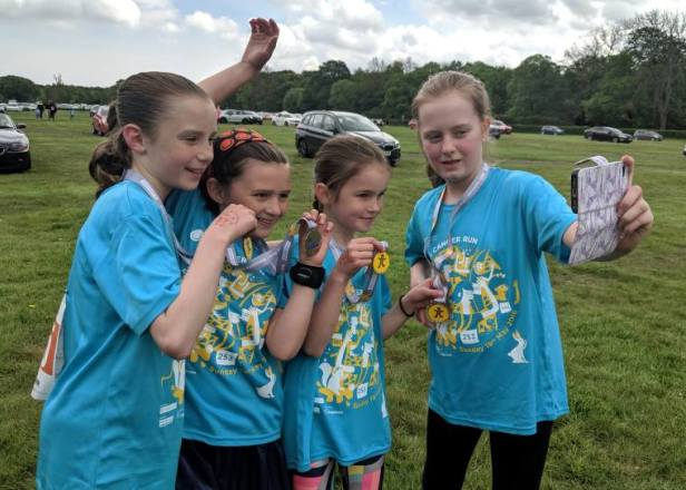 Image of 4 girls in blue cancer run T-shirts taking a selfie with medals