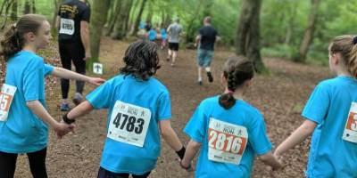 Image of 4 girls in blue race T-shirts holding hands with back to camera running through woods with other runners in front
