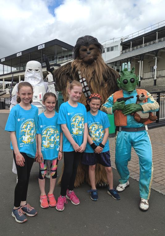 Image of 4 girls in blue race T-shirts with storm trooper, Chewbacca and alien holding gun to teddy's head