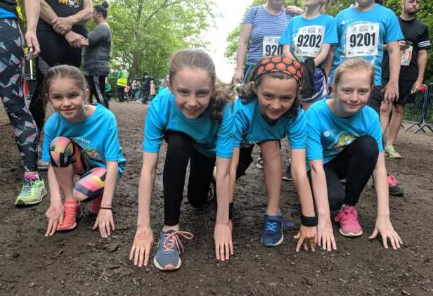Image of 4 smiling girls wearing blue Childrens Cancer Run T-shirts in race starting position down on one knee
