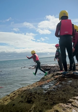 Image of child in red and black wetsuit with yellow helmet jumping from rocks into sea with others watching