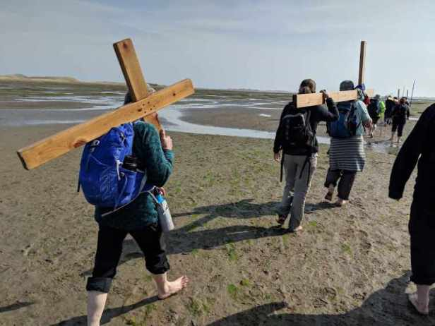 Image of group of barefoot walkers carrying wooden crosses across mud flats on causeway towards Holy Island