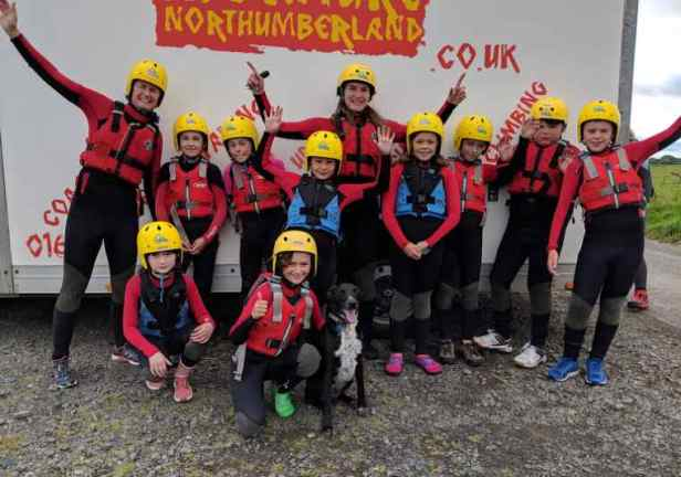 Image of group of children and adults ready for coasteering in red wetsuits and buoyancy aids, yellow helmets in front of sign for Adventure Northumberland