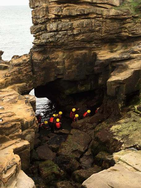 Image of group of people in red wetsuits with yellow helmets scrambling in rock stacks at coast