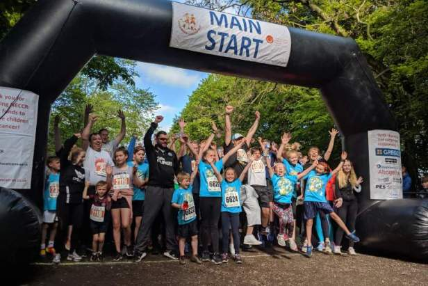Image of group of runners cheering under inflatable arch with words NECCR Main Start written on