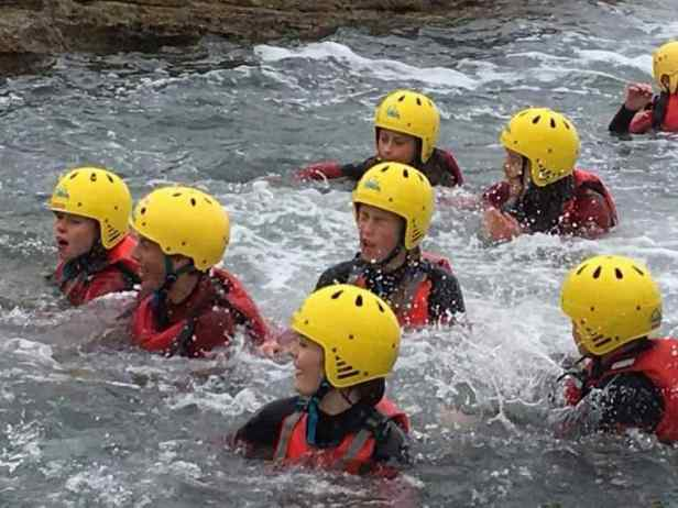 Image of group of teens in choppy water wearing red wetsuits with yellow helmets on coasteering adventure