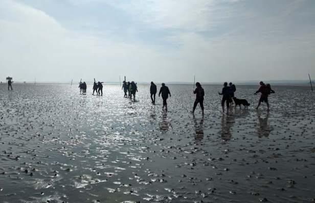 Image of group of walkers in silhouette crossing wet mudflats at Holy Island causeway carrying crucifixion cross