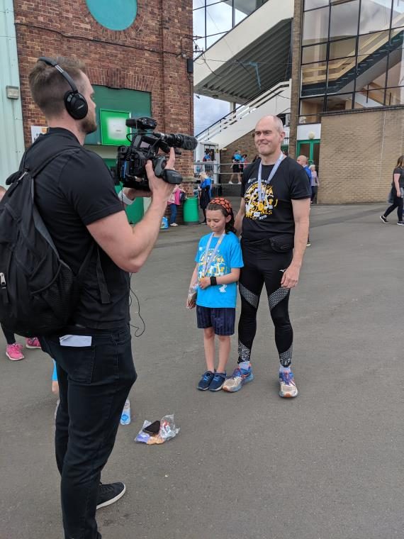 Image of man in black running gear with girl in blue T-shirt being filmed by TV camerman