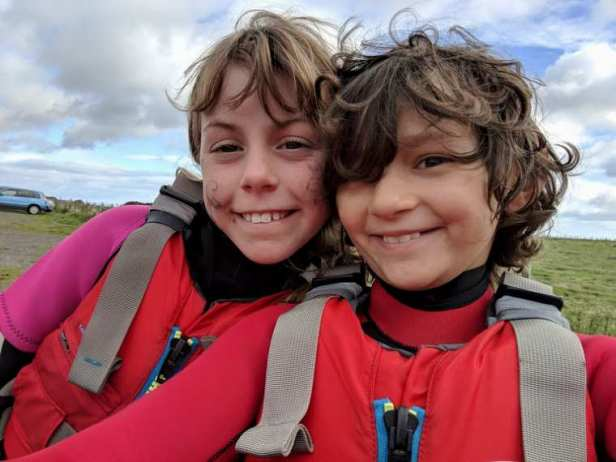 Image of two girls in red wetsuits and buoyancy aids taking selfie with field behind