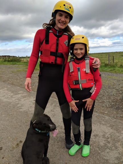 Image of woman and child in red wetsuits and buoyancy aids with yellow helmets stood by black dog on coasteering adventure