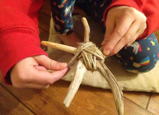 Image close up of girl's hands wrapping string around driftwood star