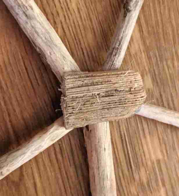 Image of 5 sticks arranged in star shape around circular piece of wood to make driftwood star