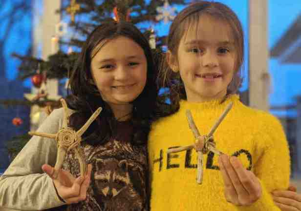 Image of two dark haired girls in purple and yellow top in front of Christmas tree holding homemade driftwood stars
