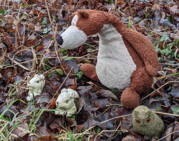 Image of Otto the cuddly brown teddy bear in woodland leaves with animal ornaments