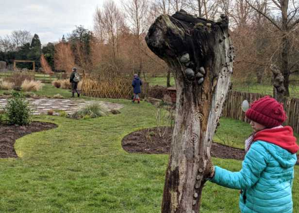 Image of girl in outdoor clothes lookign at tree stump decorated with coins and carvings in sensory garden