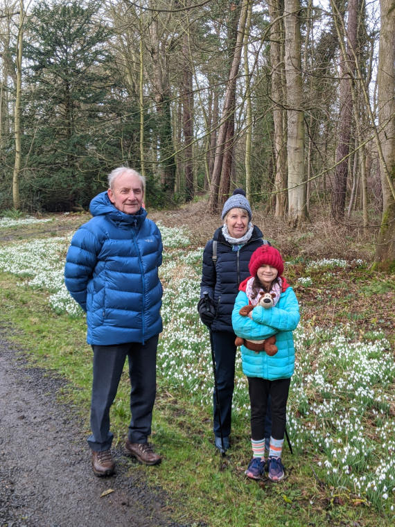 Image of man. woman and child stood in front of woodland snowdrop trail at Howick Hall Gardens