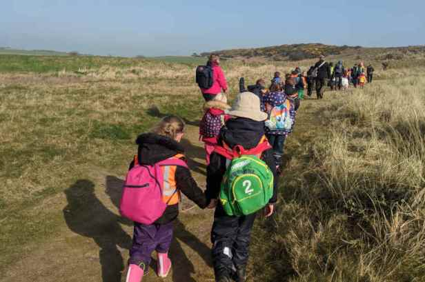 Class of children walking through sand dunes in outdoor gear to beach school