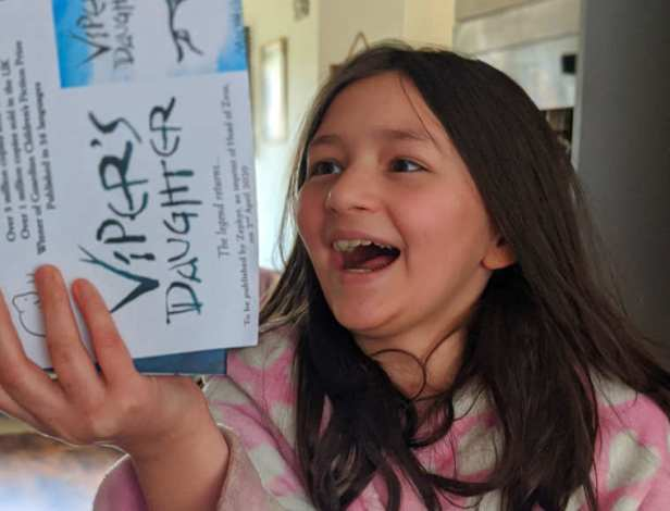 Girl smiling with joy holding copy of Vipers Daughter book by Michelle Paver