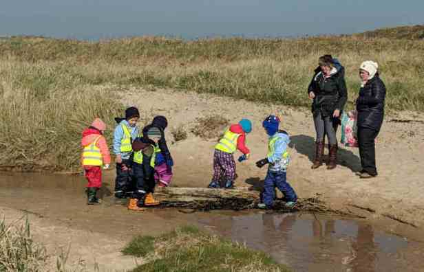 Group of young children playing on log in stream on sandy beach with dunes behind