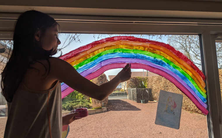 Child in silhouette painting rainbow on inside of house window during lockdown for Coronavirus Covid-19, uk 202