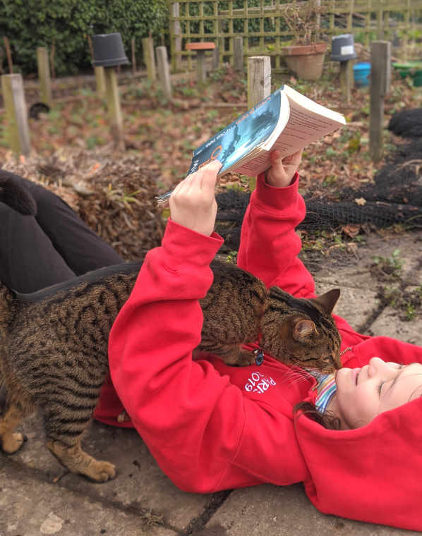 Child in red hoodie lying on ground reading blue book with tabby cat cuddling
