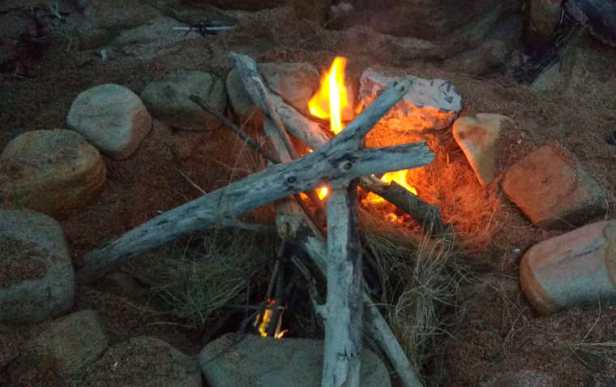 Campfire on sand with rock circle around