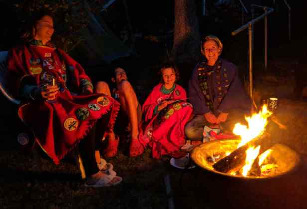 Three adults and a child wearing coloured camp blankets covered in badges around firepit campfire in a garden at night