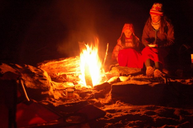 Woman and girl sitting by camp fire