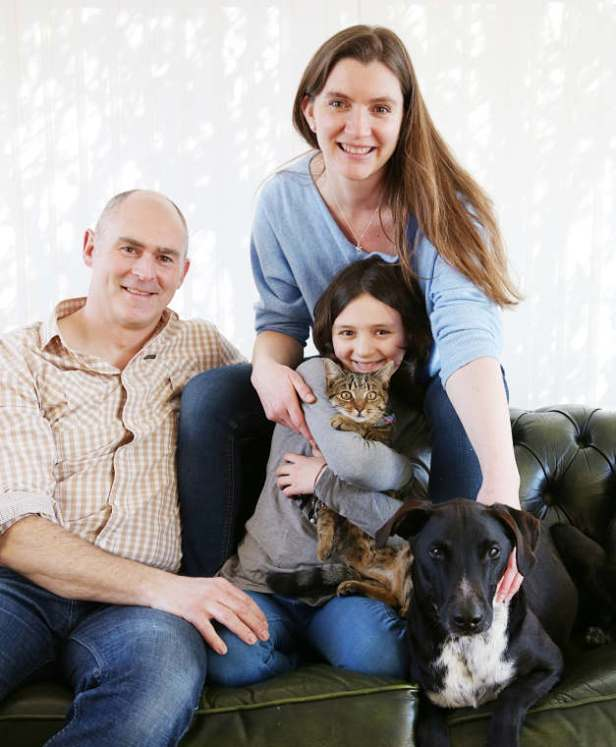 Family photo of man, woman, child, cat and dog on settee